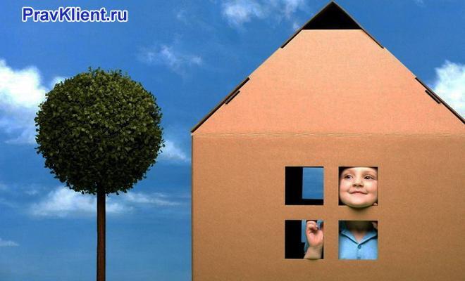 Ребенок смотрит в окно в картонном домике