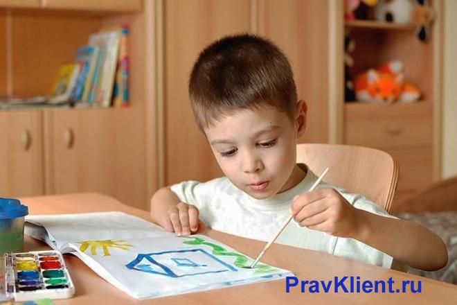 Мальчик рисует в альбоме дом