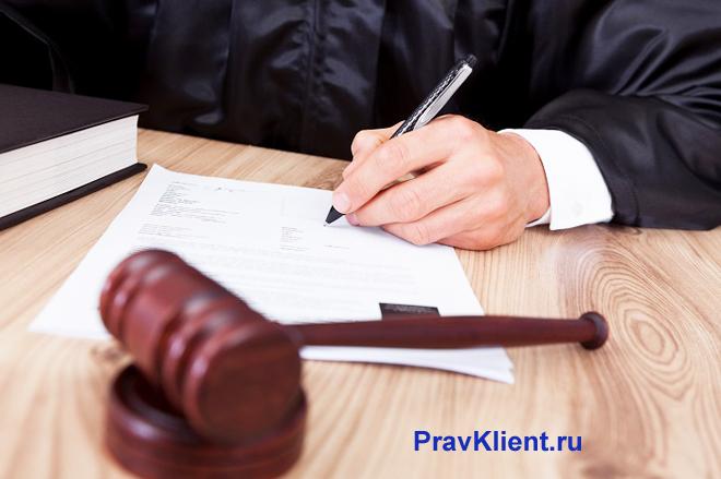 Судья заполняет документы за своим рабочим местом