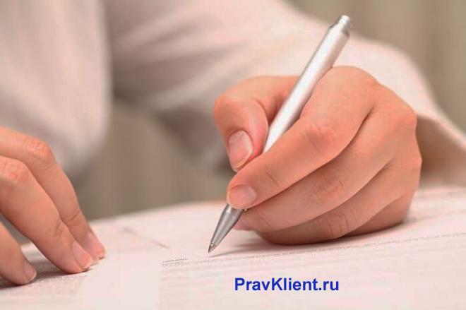 Мужчина в белой рубашке пишет ручкой на листке бумаги