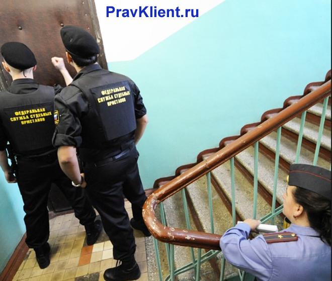 Судебные приставы на лестничной клетке стучатся в дверь