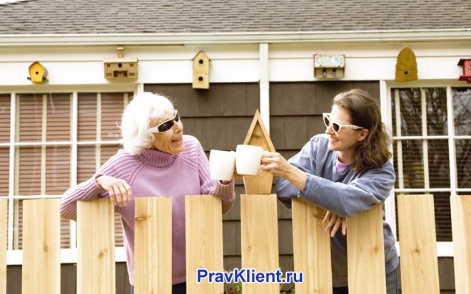 Две женщины пьют вместе чай во дворе дома