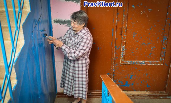 Женщина открывает ключом подсобное помещение в подъезде