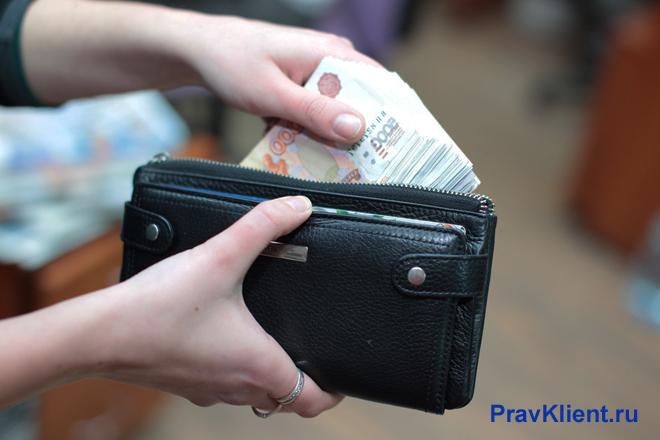 Девушка убирает деньги в кошелек