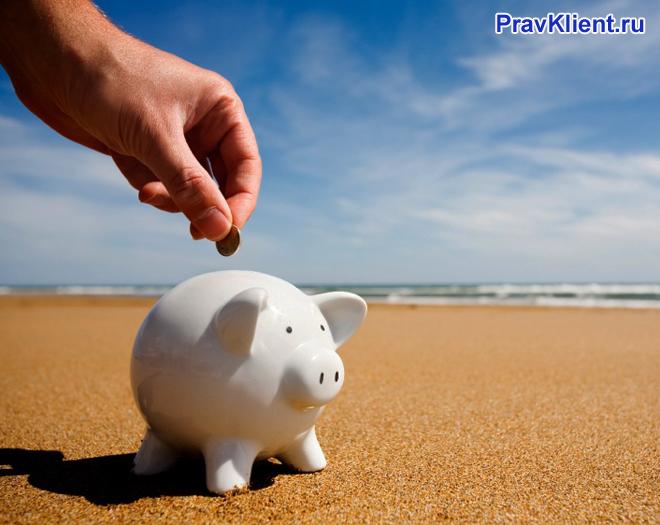 Человек кидает монетку в копилку на берегу моря