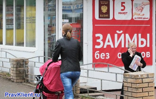 Девушка гуляет с коляской мимо рекламы микрозаймов