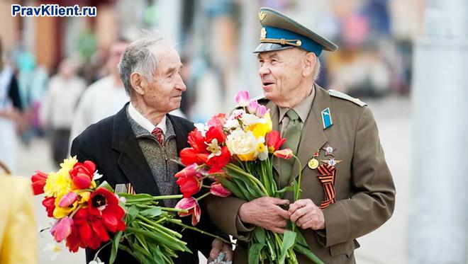 Двое ветеранов прогуливаются по площади с цветами