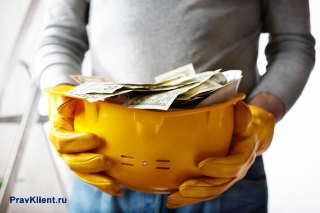 Рабочий держит в руках строительную каску с деньгами