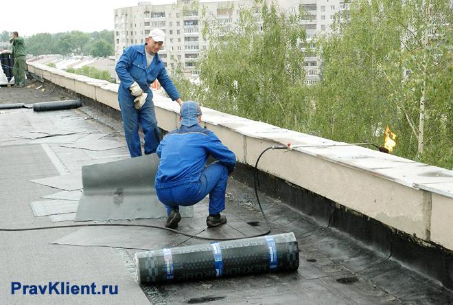 Рабочие утепляют крышу