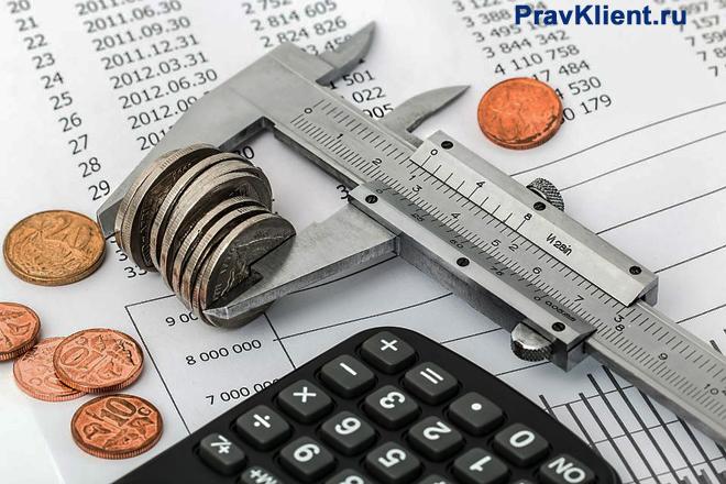Таблицы с данными на листке бумаги, калькулятор, металлическая линейка, монеты, калькулятор