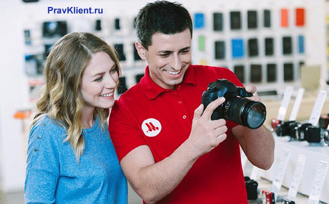 Продавец М. видео показывает покупательнице фотоаппарат