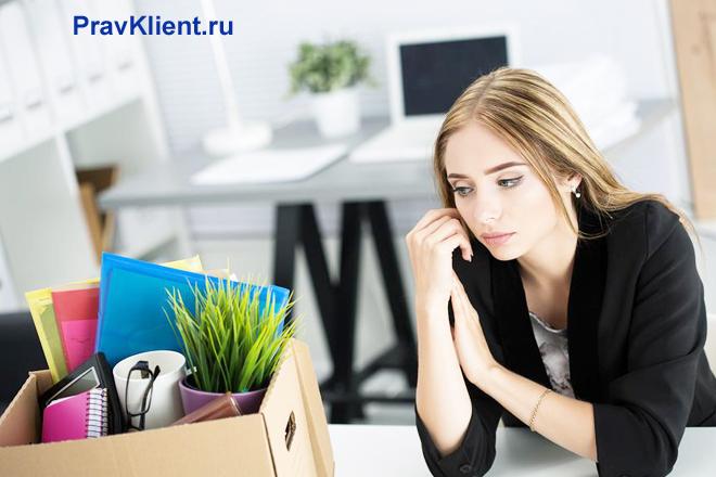 Девушка сидит за столом в офисе, рядом стоит коробка с вещами