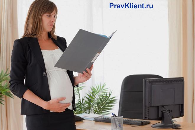 Беременная сотрудница стоит рядом со столом и читает документы