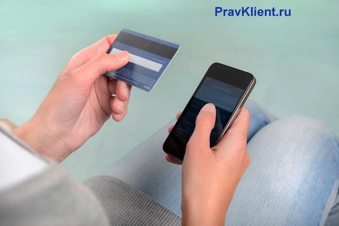 У мужчины в руках банковская карточка и телефон