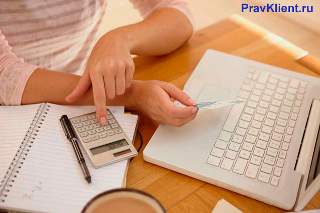 Девушка сидит за столом, считает на калькуляторе, рядом стоит ноутбук