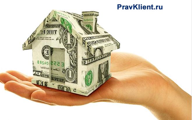 Девушка держит в руке домик из денег