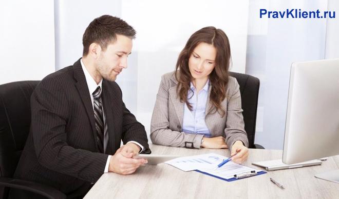 Коллеги по работе сидят за столом и подписывают документы