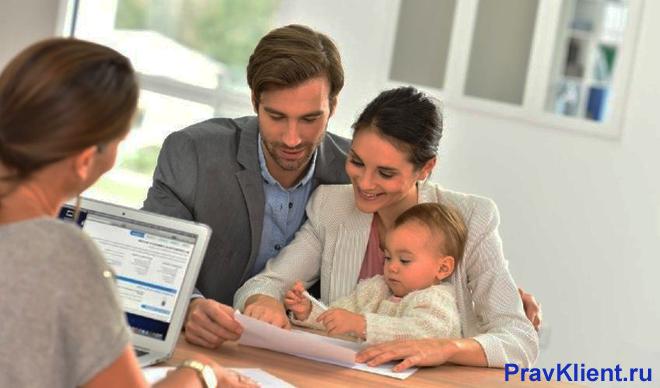 Семья с ребенком общается с женщиной насчет оформления документов
