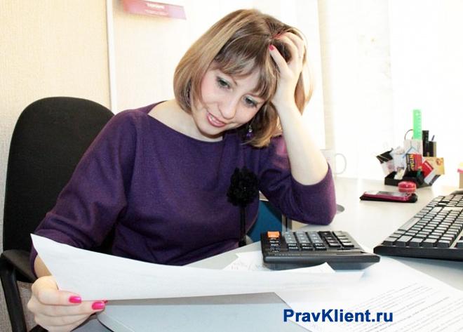 Девушка читает бумагу за своим рабочим местом