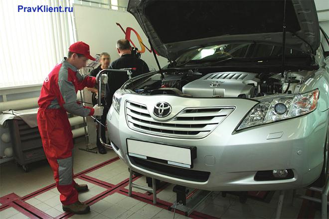 Работники автосервиса ремонтируют машину