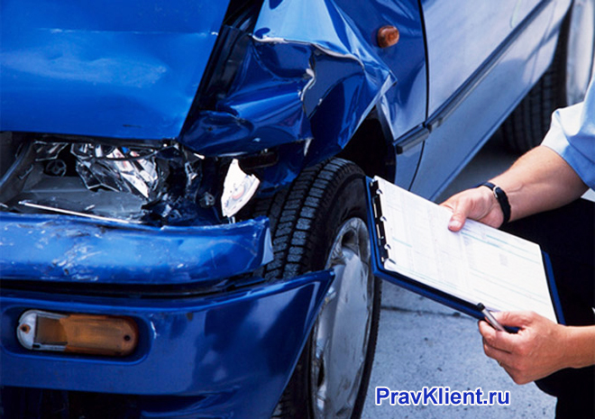 Мужчина описывает повреждения после ДТП синей машины