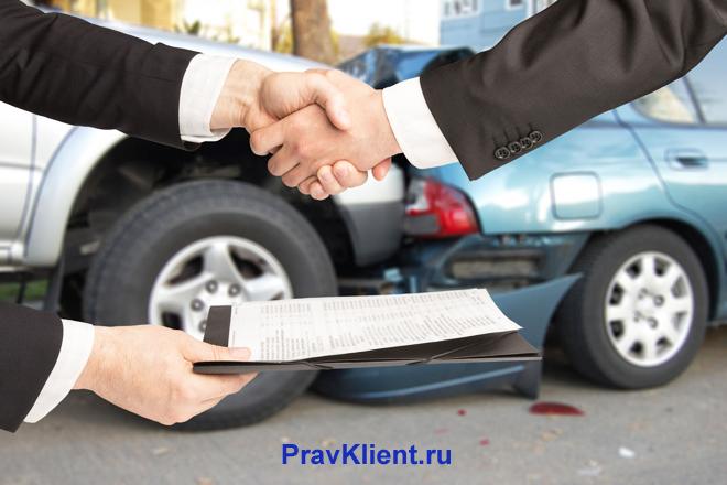 Бизнесмены жмут друг другу руки на фоне разбитых автомобилей