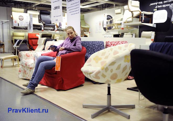 Девушка присматривает себе кресло в магазине