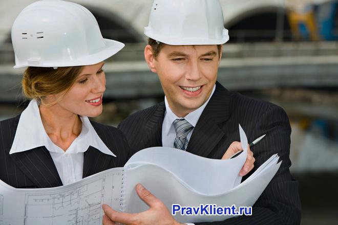 Бизнес-партнеры в строительных касках смотрят чертежи