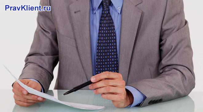 Бизнесмен в костюме читает текст на листке