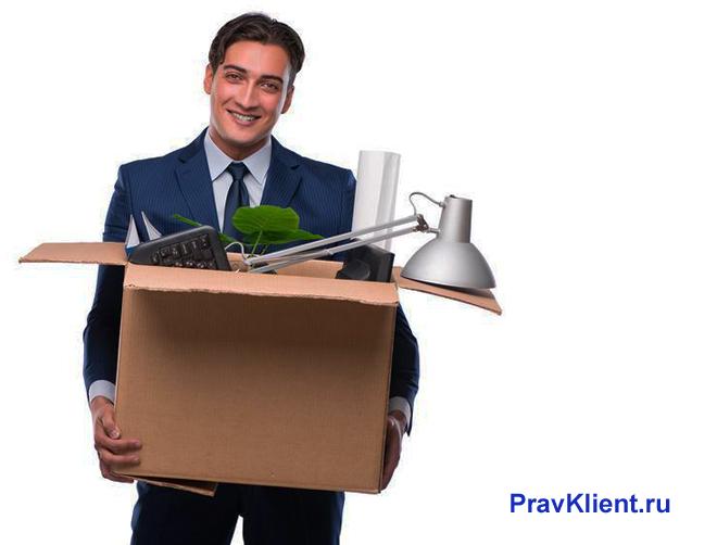 Мужчина несет в картонной коробке офисные принадлежности
