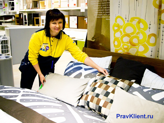 Сотрудница магазина раскладывает подушки на диване в зале