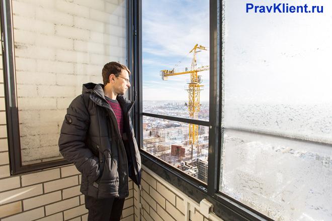 Мужчина смотрит из окна на стройку дома