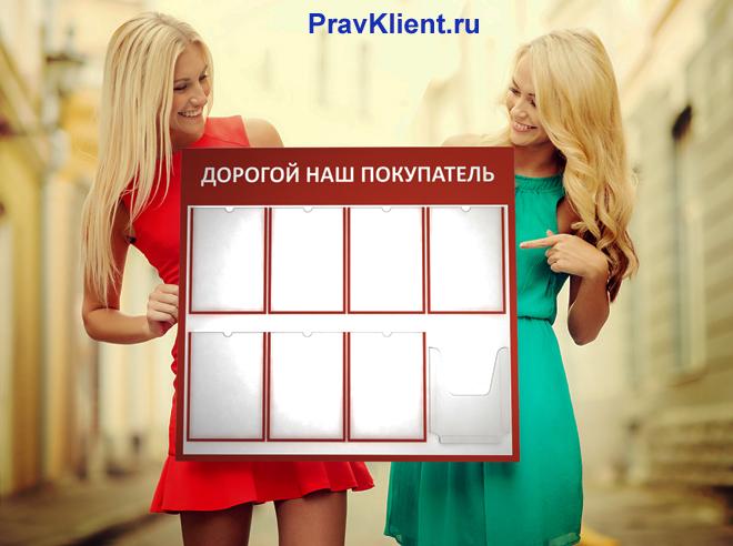 Две девушки держат в руках уголок покупателя