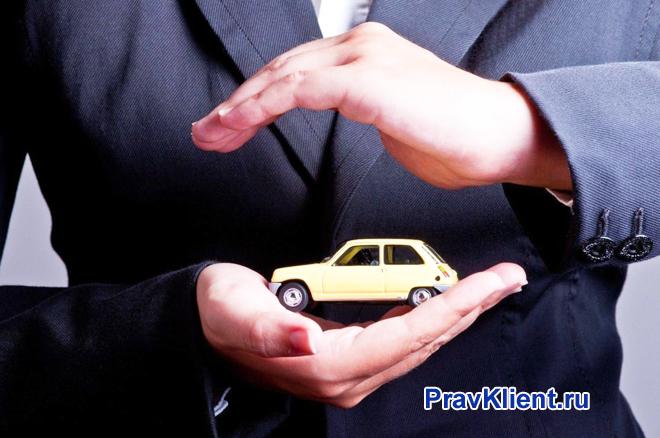 Бизнесмен держит в руках игрушечную машинку