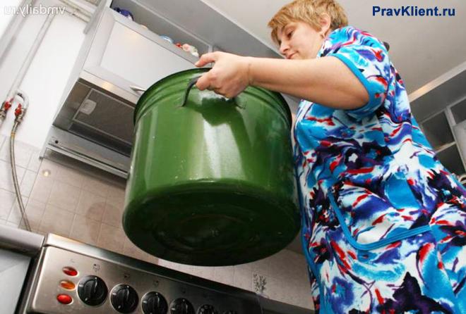 Женщина ставит большую зеленную кастрюлю на кухонную плиту
