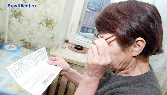 Пенсионерка смотрит платежку на кухне