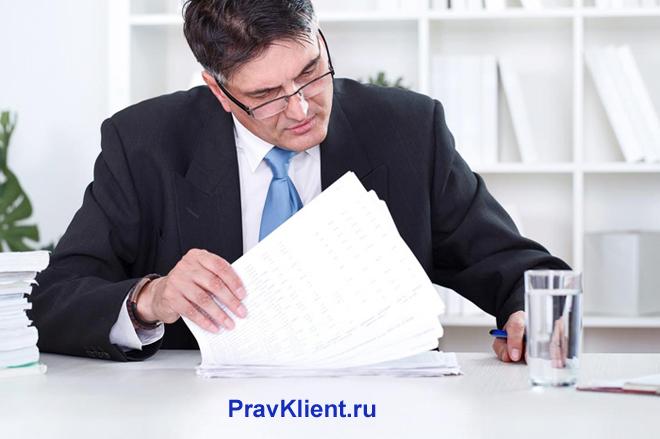 Руководитель отдела подписывает документацию в офисе
