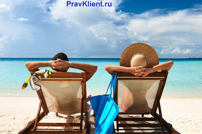 Семейная пара отдыхает на шезлонгах на берегу лазурного моря