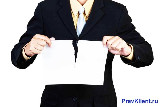 Мужчина в деловом костюме разрывает лист бумаги пополам