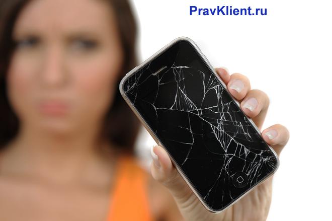 Девушка держит в руке разбитый телефон