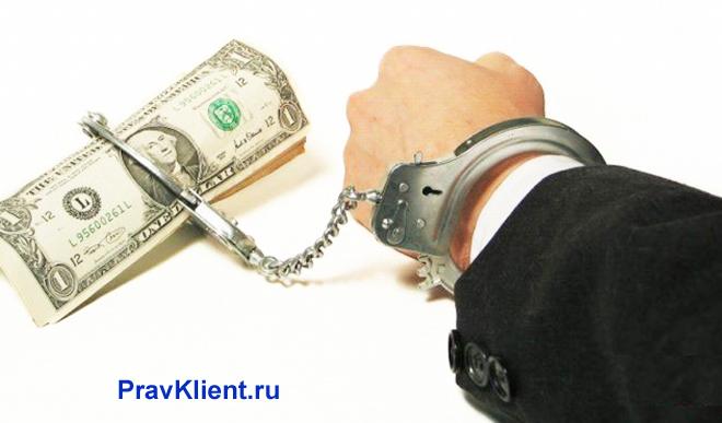 Бизнесмен прикован наручниками к банкноте