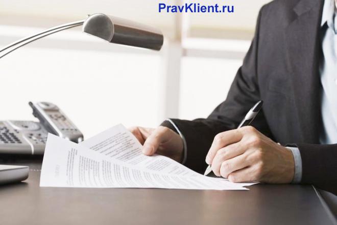 Бизнесмен работает за столом, пишет заявление