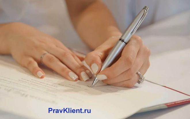 Девушка пишет претензию на листке бумаги