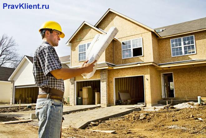 Мужчина в строительной каске смотрит документы на фоне частного дома