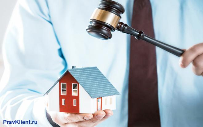 Мужчина в голубой рубашке держит в руках макет дома и молоточек