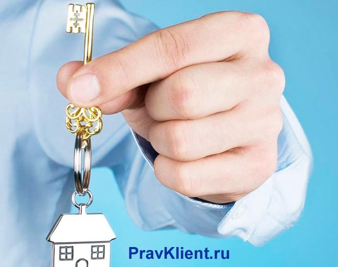 Мужчина держит в руке ключи от дома