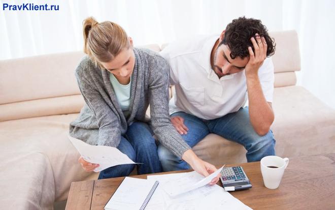 Семейная пара разбирается с документами в гостиной