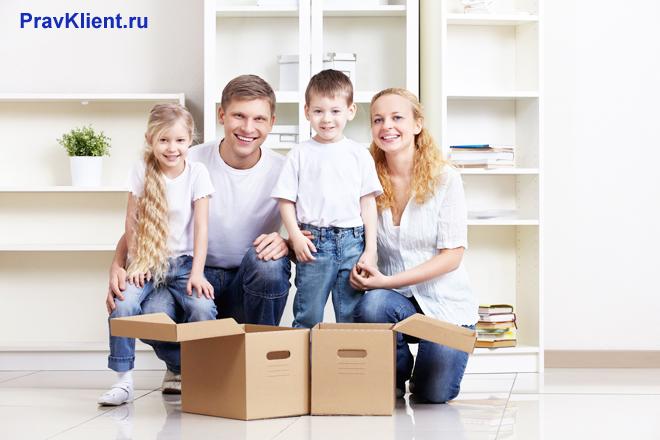 Семья с двумя детьми собирает вещи в доме
