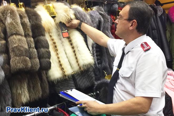 Сотрудник Роспотребнадзора проверяет бирки на меховых изделиях
