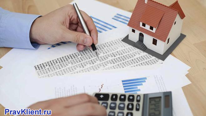 Мужчина заполняет документы, считает на калькуляторе, рядом стоит дом